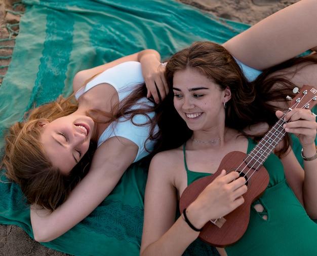 Niña tocando el ukelele para su amiga mientras se está acostado en la playa