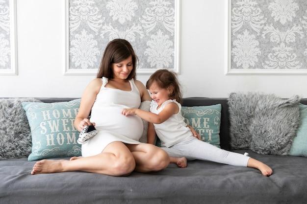 Niña tocando el vientre de su madre