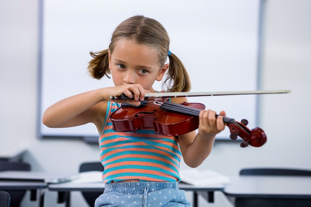 Niña tocando el violín en el aula
