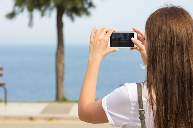 La niña toma fotos de la belleza del mar.