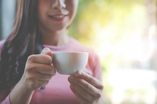 La niña está tomando café con placer en la cafetería.