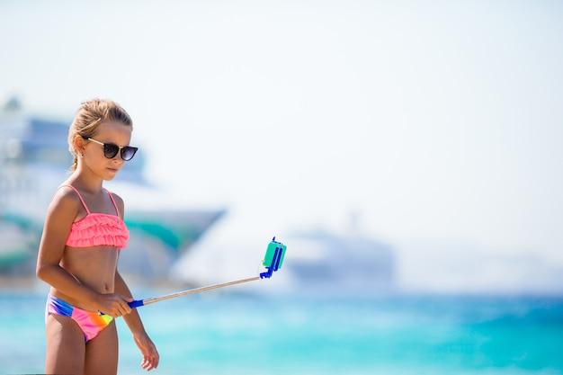 Niña tomando selfie por su teléfono inteligente en la playa.