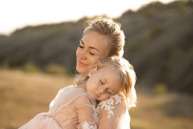 Una niña se está tomando el sol y se está quedando dormida sobre su madre