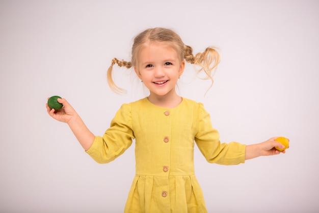 La niña tooddler hace malabares con los huevos y sonríe alegremente