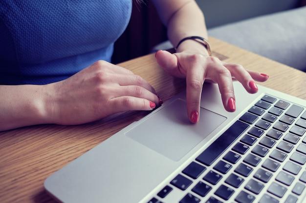 La niña trabaja en la computadora portátil en la cafetería. las manos están escribiendo en el teclado.