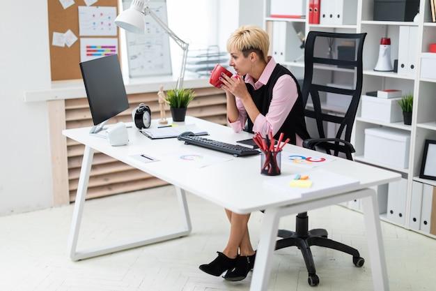 La niña trabaja en la oficina en la computadora y sostiene una taza.