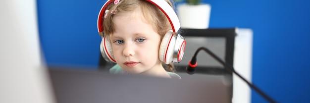 Niña trabaja con portátil en casa. concepto de educación escolar en línea.
