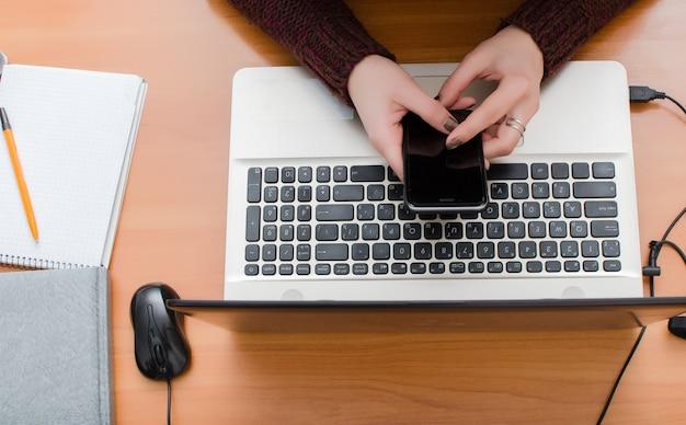 La niña está trabajando en la computadora y sostiene un teléfono móvil