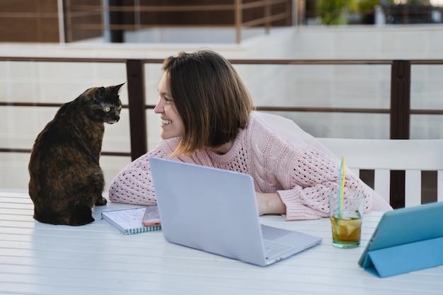 Niña trabajando remotamente en la terraza de su casa con su mascota
