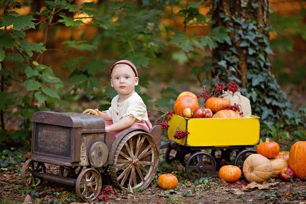 Niña en tractor con un carro con calabazas