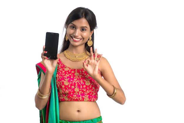 Niña tradicional india joven que usa un teléfono móvil o un teléfono inteligente y muestra un teléfono inteligente con pantalla en blanco