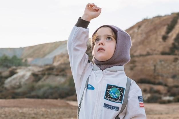 Niña en traje de astronauta en la naturaleza