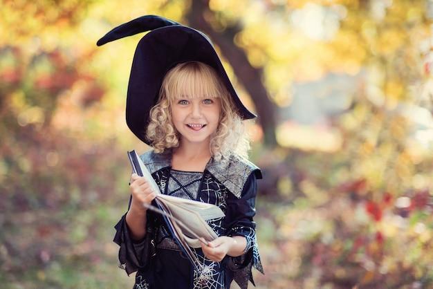 Niña en traje de bruja celebrar halloween al aire libre y divertirse.