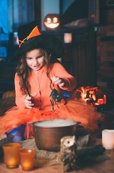 Niña en un traje de bruja poniendo araña en bombín