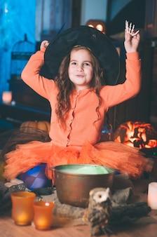 Niña en un traje de bruja con varita mágica mirando hacia arriba