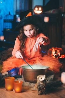 Niña en traje de bruja con varita mágica