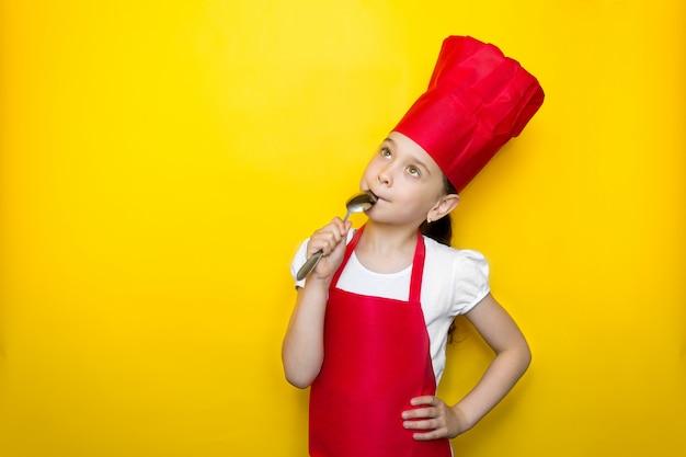 Niña en traje de chef rojo lame la cuchara, sueña, delicioso sabor en amarillo