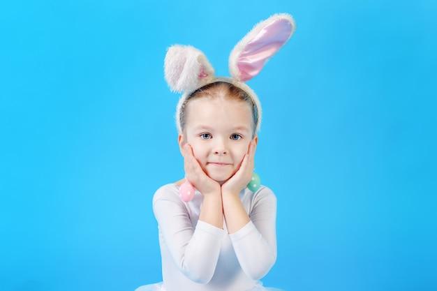 Niña en un traje de conejito de pascua blanco. hermosa niña emocional.