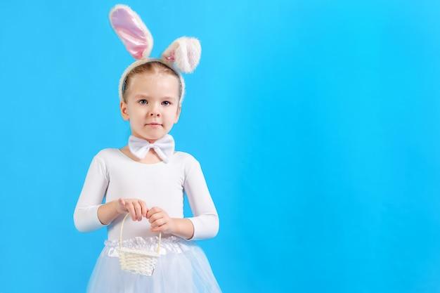 Niña en un traje de conejito de pascua blanco. el niño sostiene una pequeña canasta. copia espacio