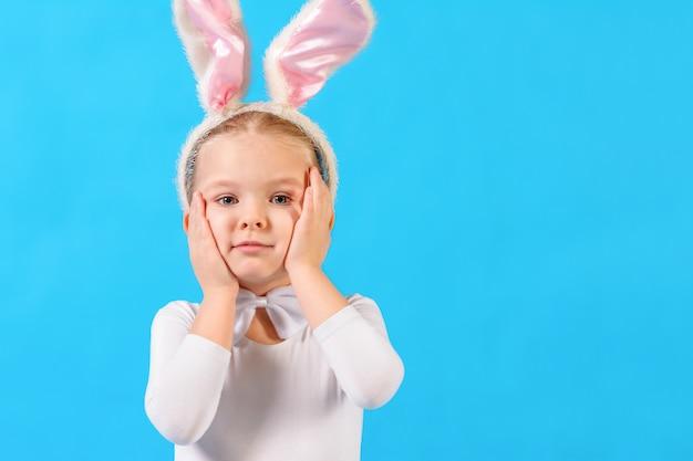 Niña en un traje de conejo blanco sobre una pared azul. el niño sostiene su cabeza.