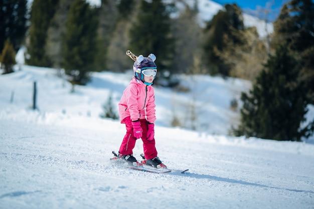 Niña en traje de esquí rosa esquiar en ladera cuesta abajo. actividad recreativa de deportes de invierno.