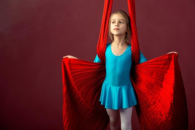 Niña en un traje de gimnasia azul preparado para el rendimiento con una cinta roja y aireada sobre un fondo rojo pálido