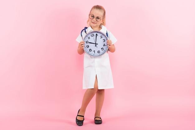 Niña en traje de médico con relojes