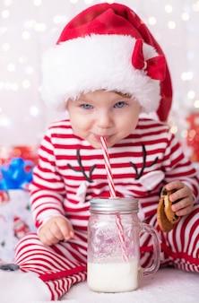 Niña en un traje de navidad con regalos cerca del árbol de navidad bebe leche y decora un ciervo