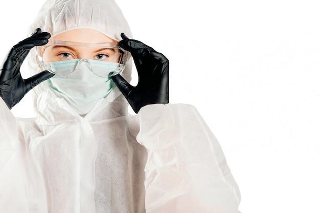 Una niña con un traje protector y una máscara y gafas para proteger la salud de enfermedades virales, epidémicas e infecciosas. nuevo covid-19. concepto de pandemia del virus corona. detener el virus
