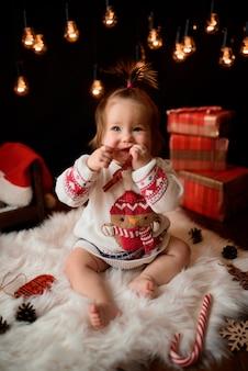 Niña en un traje rojo de navidad con guirnaldas retro se sienta sobre una piel