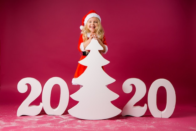 Niña en un traje de santa está sosteniendo un gran árbol de navidad blanco, junto a los grandes números blancos 2020 sobre un fondo rojo.