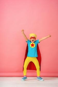 Niña en un traje de superhéroe con capa roja y sombrero muestra lo fuerte que es.