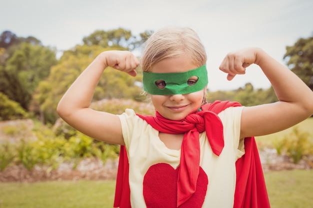Niña con traje de superhéroe contraer bíceps