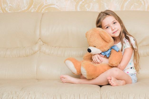 Niña tranquila abrazando oso de peluche