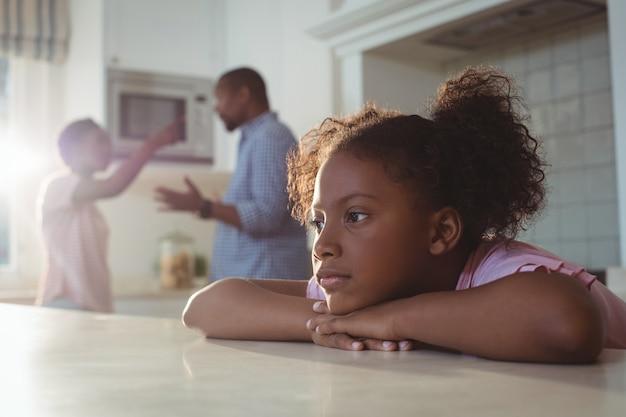 Niña triste escuchando a sus padres discutiendo en la cocina