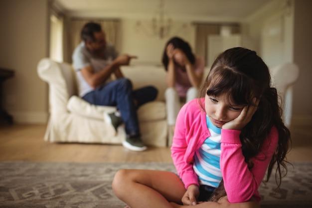 Niña triste escuchando a sus padres discutiendo
