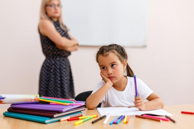 Niña triste en la escuela en el escritorio
