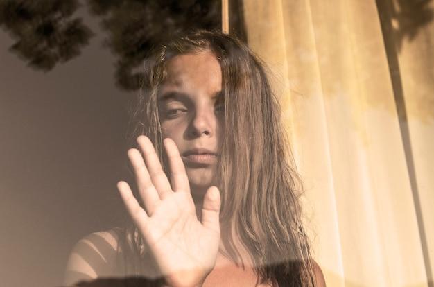Niña triste mirando por la ventana llorando, foto incolora de la vendimia
