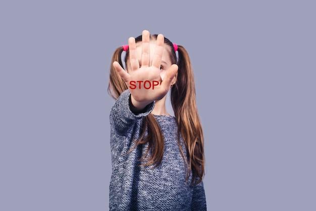 Niña triste muestra señal de stop de mano. concepto detener el abuso infantil. aislado en superficie gris