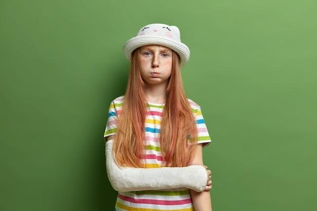 La niña triste y ofendida sopla las mejillas, ha disgustado una mueca después de una pelea con la madre, usa un sombrero y una camiseta a rayas, aislada sobre una pared verde. expresiones faciales negativas, concepto de mal humor