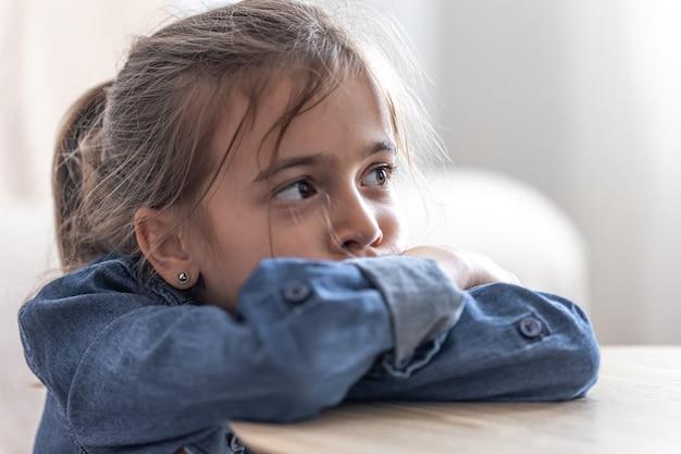 Niña triste sentada en la mesa en la escuela, concepto de regreso a la escuela.