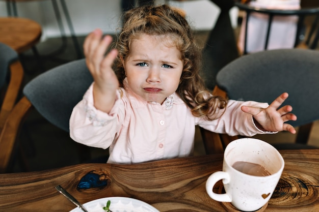 Niña triste está sentada en una mesa en un restaurante