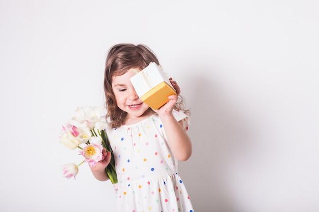 Niña con tulipanes y caja con regalo para mamá
