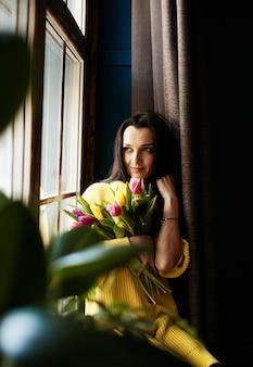 Una niña con tulipanes mira por la ventana.