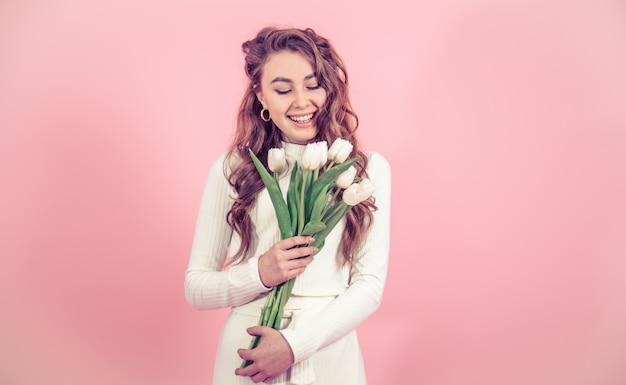 Niña con tulipanes en una pared de color