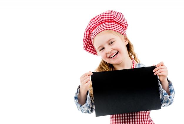 Niña en uniforme de chef con papel en blanco