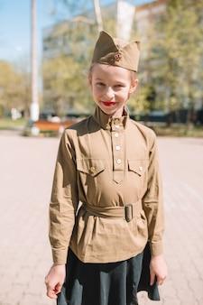 Niña en uniforme militar en el día festivo de la victoria