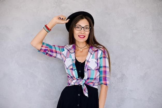 Niña urbana sonriente con gafas y sombrero