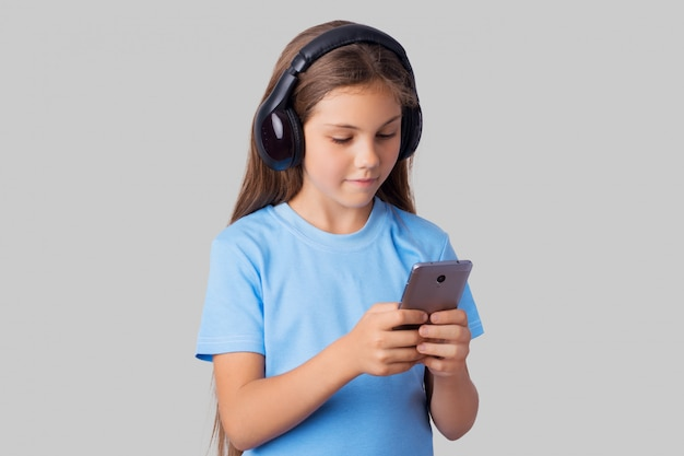 Niña usando auriculares inalámbricos bluetooth para escuchar audiolibros en su moderno teléfono inteligente