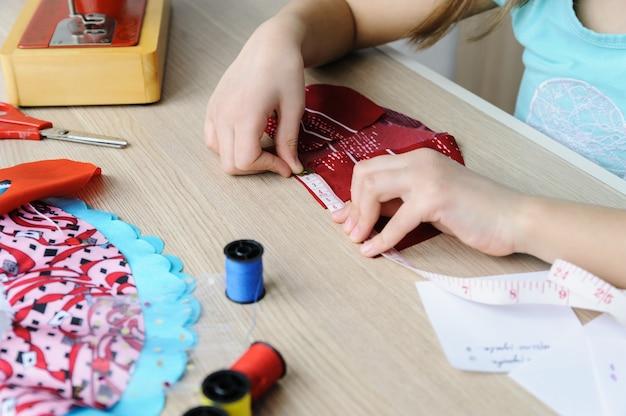 Una niña está usando una cinta métrica para medir un vestido para una muñeca